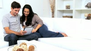 stock-footage-attractive-young-heterosexual-hispanic-couple-relaxing-home-couch-wireless-tablet