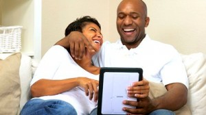 stock-footage-young-african-american-couple-relaxing-on-home-sofa-using-a-wireless-tablet